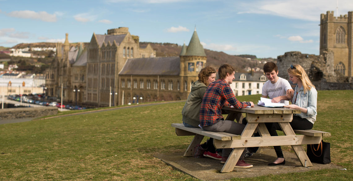 Group of people sitting at a picnic table in the castle grounds in Aberystwyth